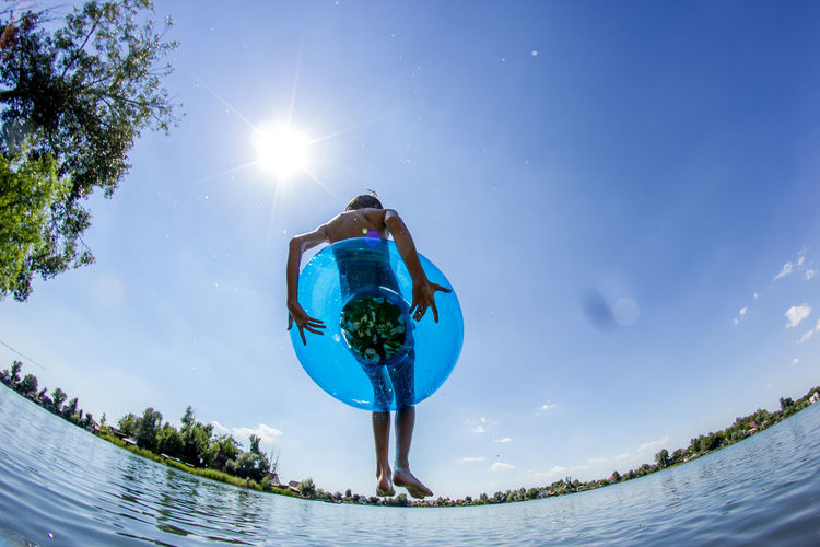 Fish-eye lens view of boy jumping with inflatable ring in lake