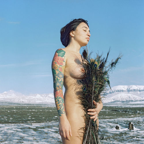 Naked woman standing by sea