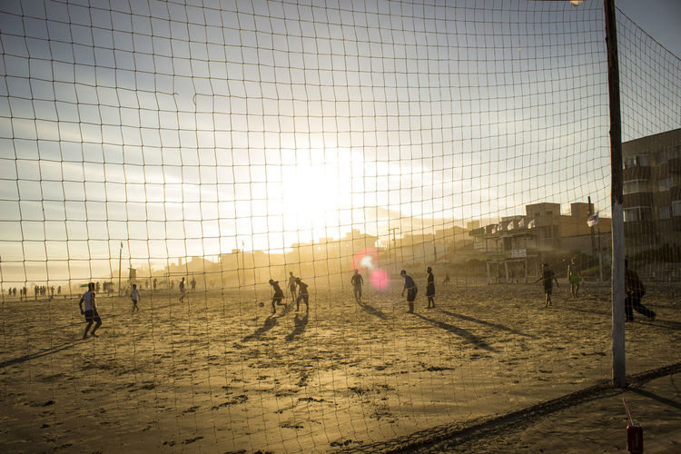 People playing soccer at sandy beach against sky during sunset
