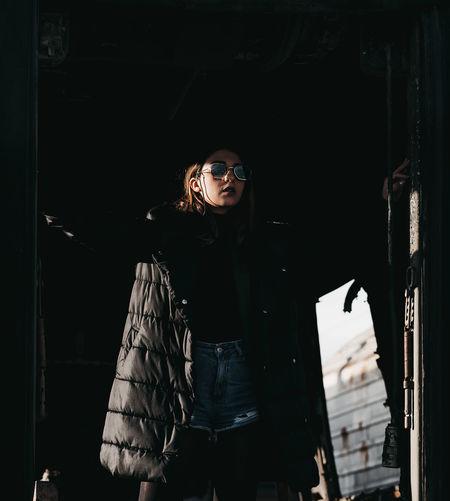 Fashionable woman standing at doorway looking away