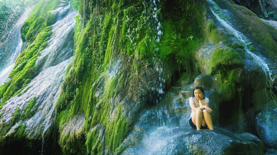 Portrait of woman sitting against waterfall in forest