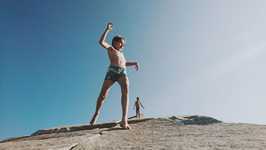 Low angle view of shirtless boy standing against clear sky