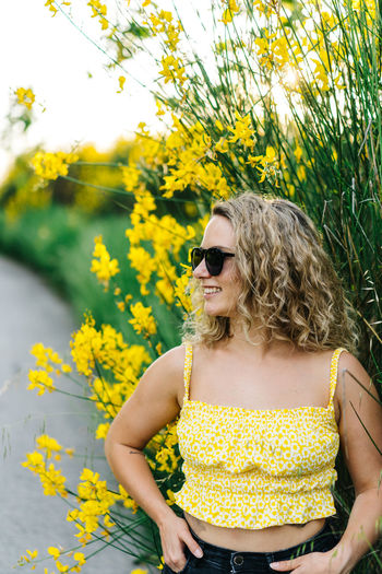 Midsection of woman with yellow flowers against plants