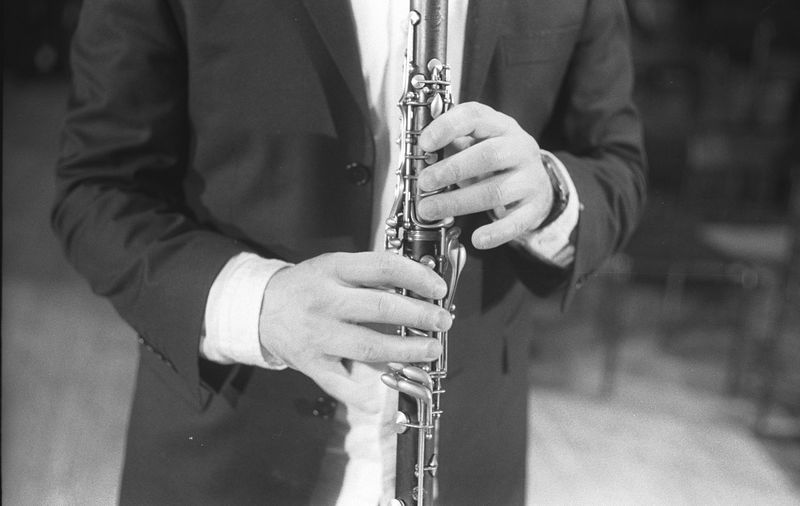 Midsection of man playing clarinet while standing at studio