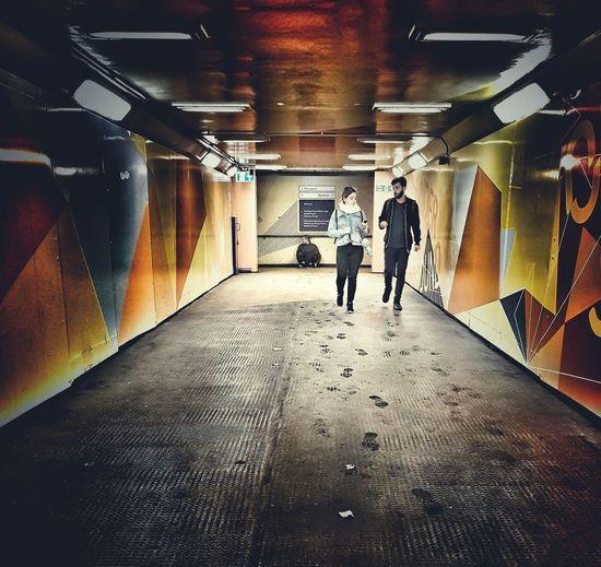 People in illuminated underground walkway
