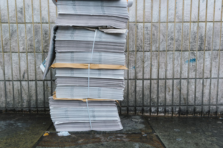 stack of news paper at the street Brick Wall Copy Space Weathered Architecture Communication Dirty Fake News Information Large Group Of Objects Many News Newspaper No People Old Pattern Stack Street Wall - Building Feature Warehouse Wood - Material