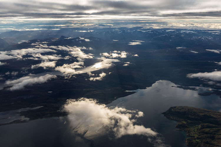 Early morning view with sunbeams seen from airplane over mountains and fjords Cloudscape Dramatic Sky Natural Light Nature Sunlight Above Aerial View Awe Beauty In Nature Cloud - Sky Day Fjord Landscape Mountain Mountain Range Natural Phenomenon Nature Nordland County Outdoors Scenics - Nature Sea Sky Sunbeam Sunrise Water