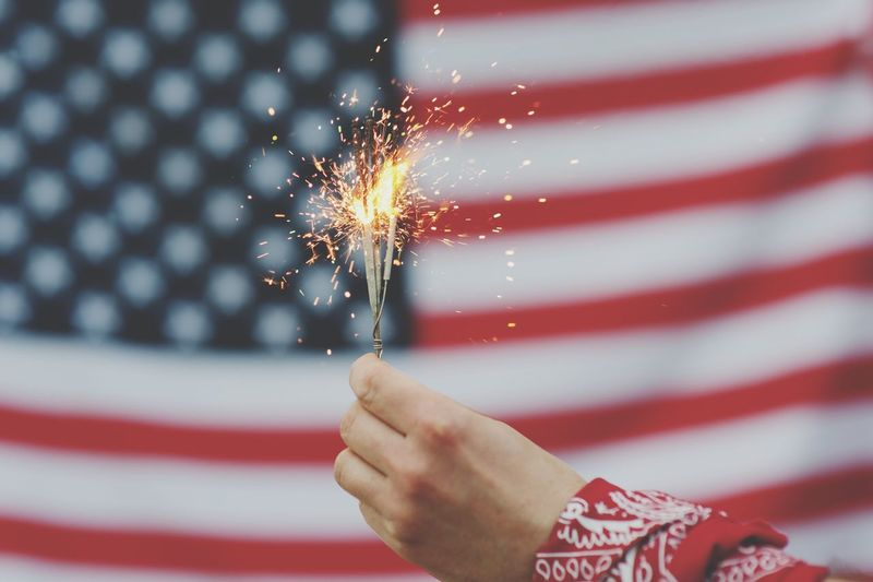 Cropped hand holding illuminated sparkler against american flag