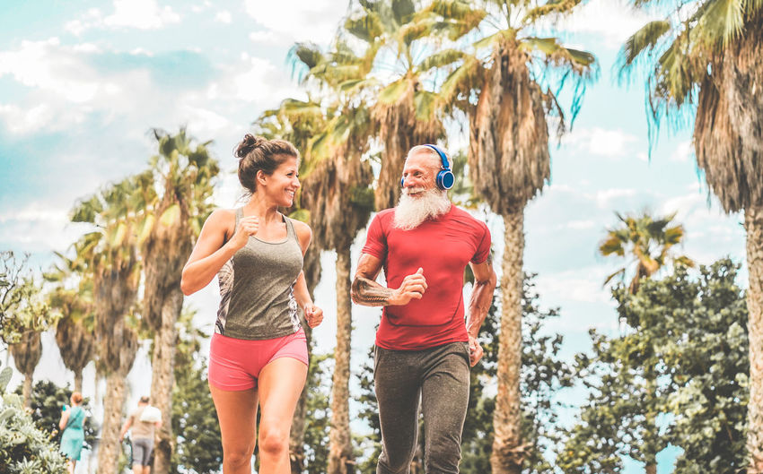 Smiling Friends Jogging Against Palm Trees