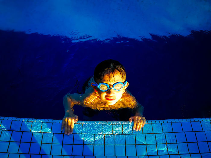 Swimming in the blue swimming pool. Kids Water Fun Happy Swimming Family Happiness Blue Outdoors Family Time Malaysia Swim Swimming Pool Kids Being Kids Family Fun Asian  Swimming Time Family❤ Active Lifestyle  Malaysian Outdoor Photography Asian Family Active Kids Real People One Person Front View Child Portrait Childhood Males  Leisure Activity Lifestyles Looking At Camera Men Illuminated Nature Boys Underwater Pool Eyewear Human Face
