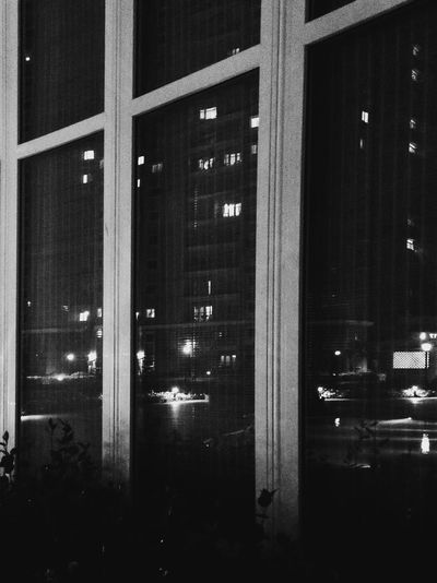 Illuminated buildings seen through glass window at night