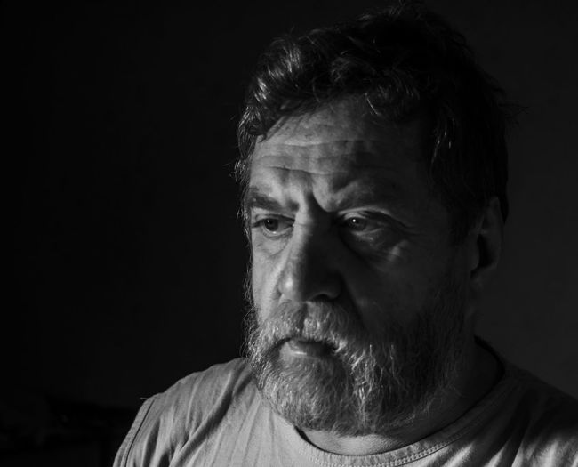 sad middle-aged bearded man Bearded Black And White Black Background Casual Clothing Caucasian Close-up Headshot Leisure Activity Lifestyles Looking Away Low Light Man Middle-aged One Mid Adult Man Only Person Sad Studio Shot Young Adult Young Men