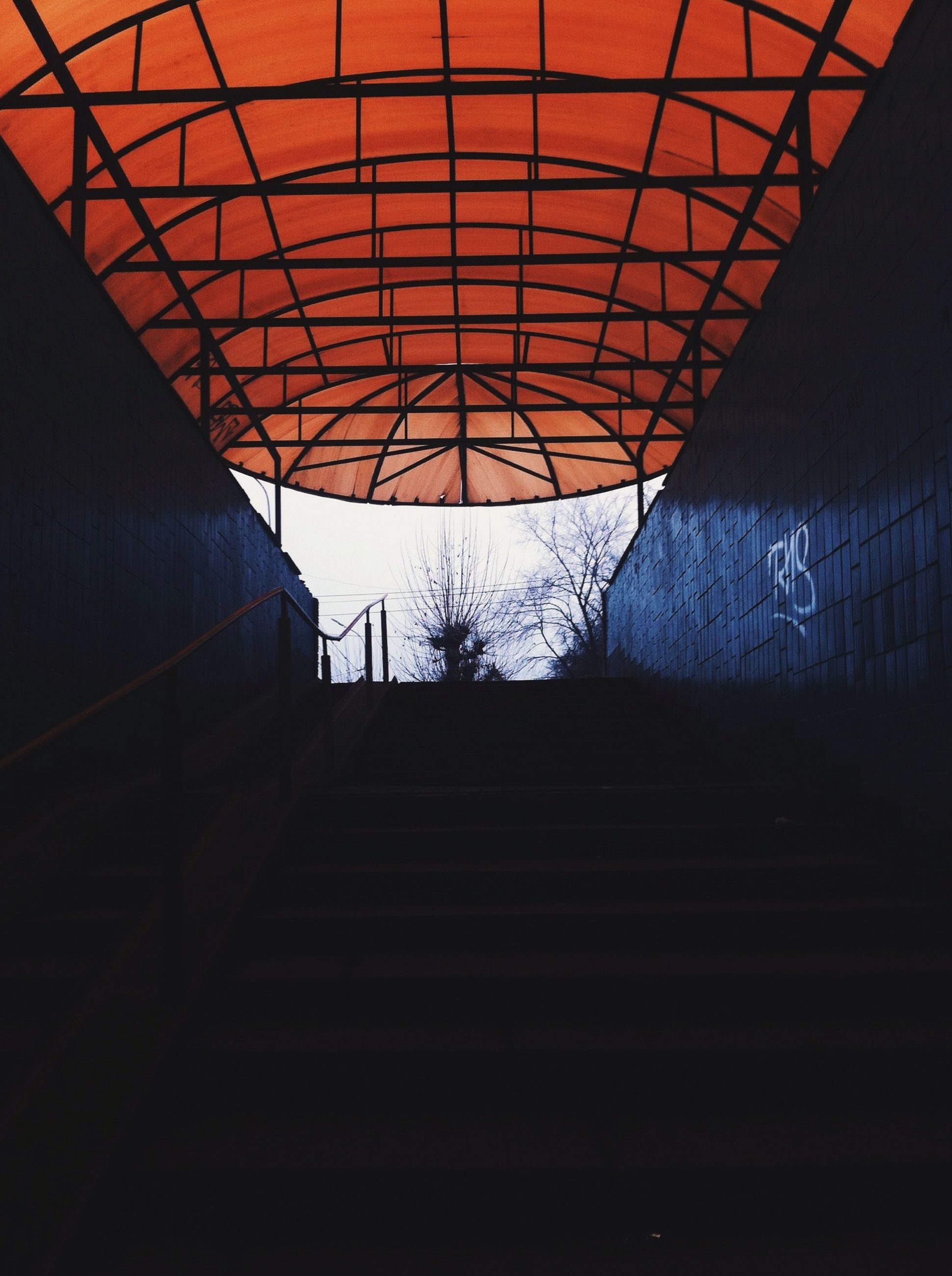 indoors, low angle view, built structure, architecture, ceiling, transportation, the way forward, no people, silhouette, steps, metal, railing, diminishing perspective, wall - building feature, building, staircase, day, illuminated, steps and staircases, connection