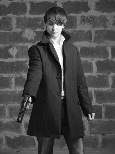 Young Man Holding Gun Against Wall