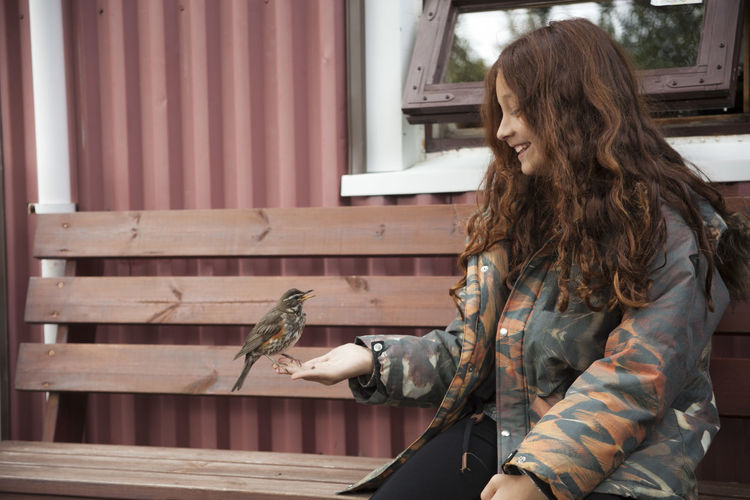 Best friends Animal Love Animal Themes Architecture Autumn Colours Bird Bird Lovers Casual Clothing Day Girl Happy Iceland Laughing Leisure Activity Nature One Animal Optimistic Outdoors People Real People Red Hair Side View Sitting Sitting Outside Wood - Material Young Adult
