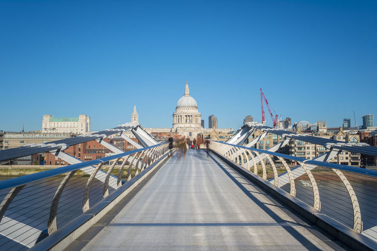 View of footbridge in city against clear sky