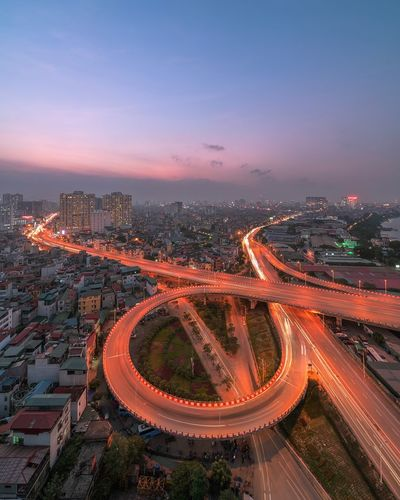 Aerial view of light trails on road amidst buildings against sky during sunset
