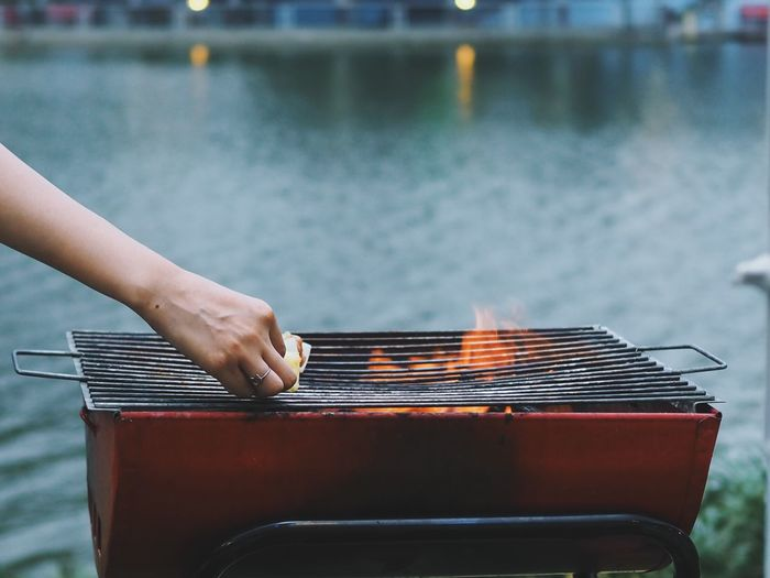Cropped hand of woman holding food over barbecue grill by lake