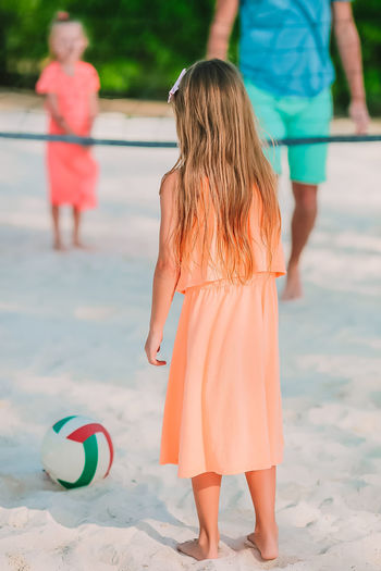 Rear view of girl playing volleyball on beach