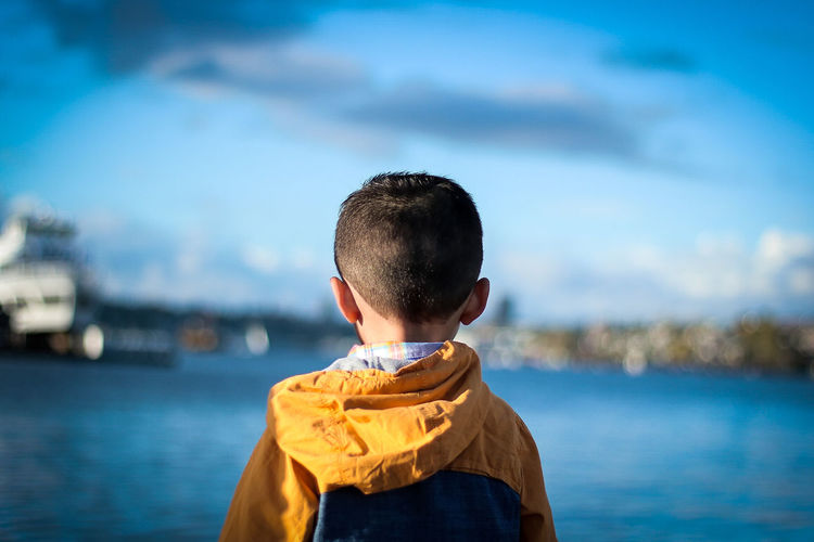 Rear view of boy standing in sea against sky