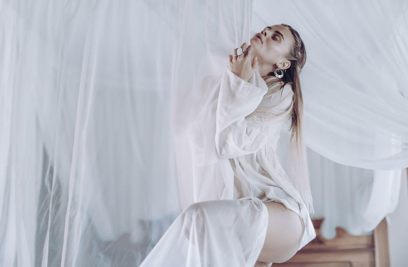 Young hippie girl blonde on a background of white transparent curtains