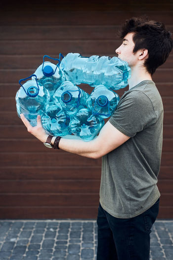 Young man throwing out empty used plastic water bottles into trash bin