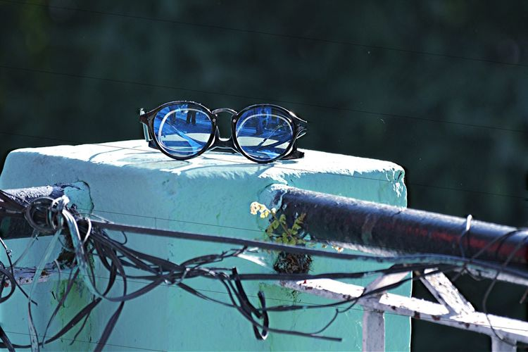 Close-up of sunglasses on railing