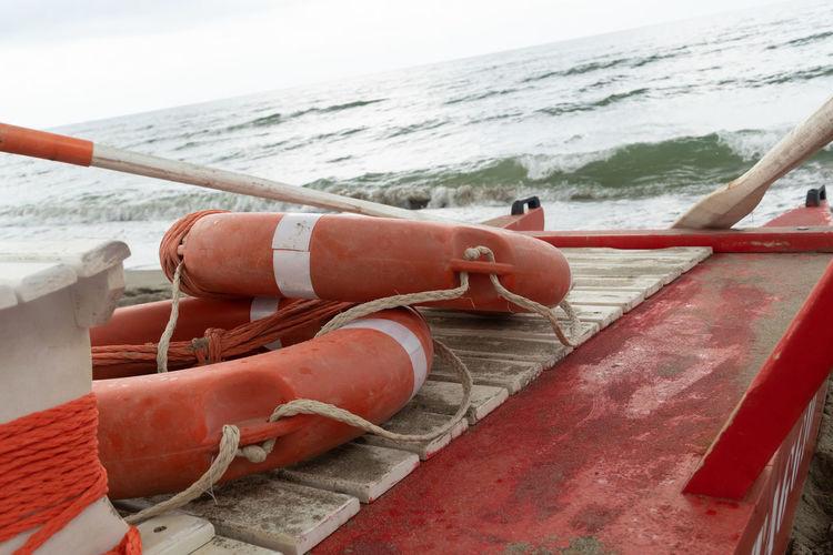 Orange lifebuoys with ropes on a rescue rowing catamaran