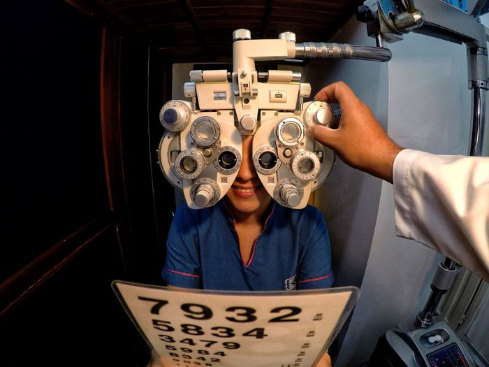 Cropped hand of doctor examining patient eyes using optical instrument