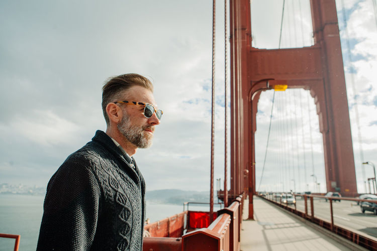Profile portrait of adult man with beard standing on the golden gate bridge during cloudy weather