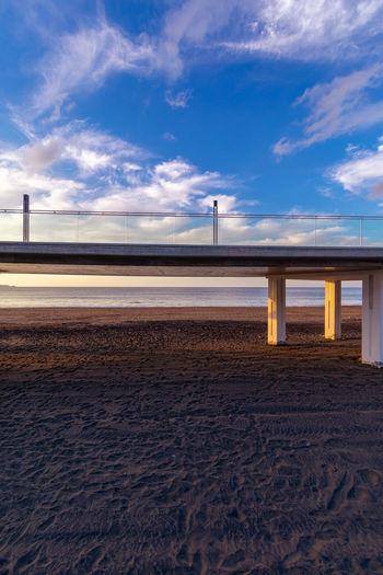 Bridge over beach against sky