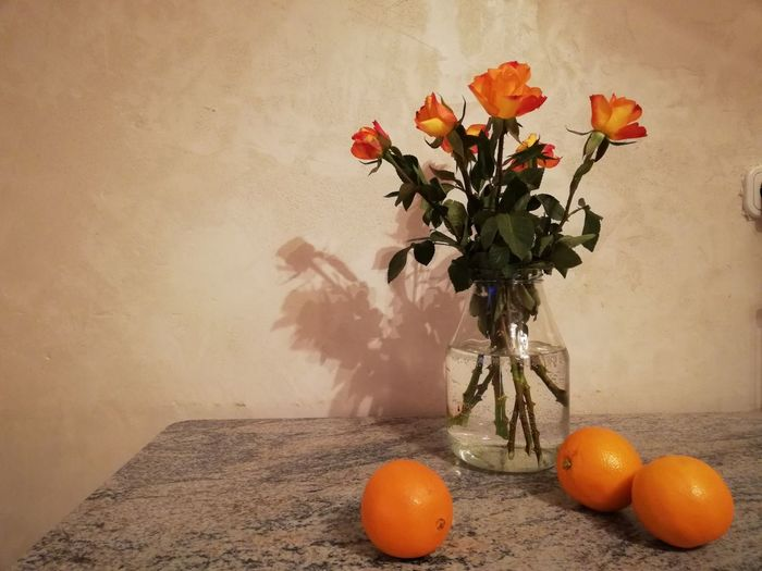 Close-up of orange flower vase on table against wall