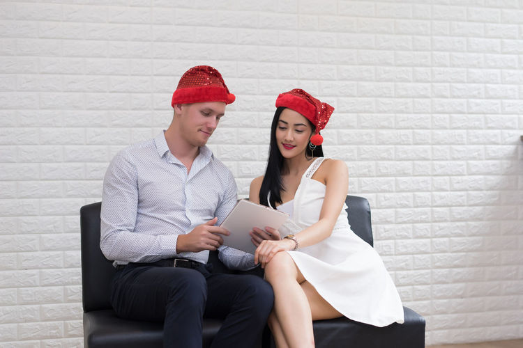 Couple using digital tablet while sitting on seat against white brick wall