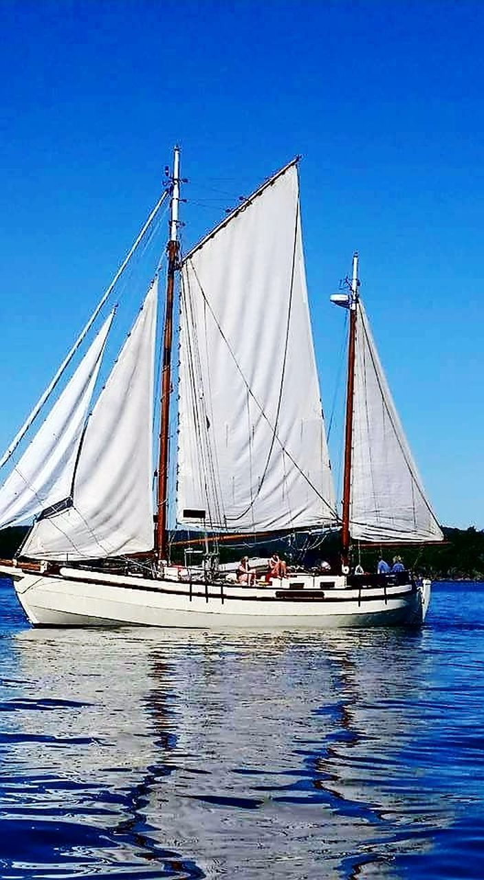 nautical vessel, sailboat, blue, mast, transportation, sea, sailing, sailing ship, mode of transport, sky, outdoors, water, tall ship, travel destinations, no people, day, sunlight, ship, clear sky, nature, yacht, harbor, beauty in nature, yachting
