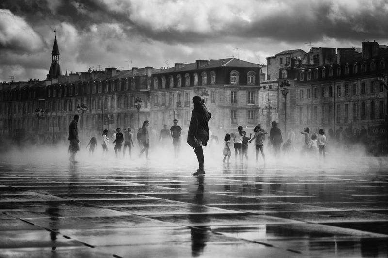 People at fountain by buildings against cloudy sky