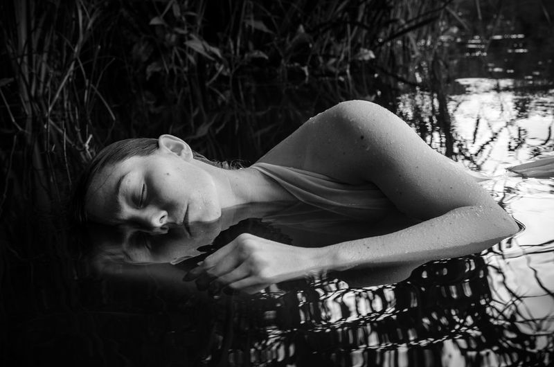 Close-up of young woman sleeping in pond