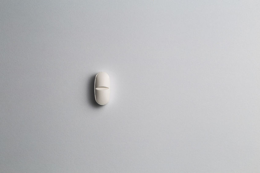 close up of a pill in isolated background Copy Space Studio Shot White Background Indoors  No People Healthcare And Medicine Pill Medicine Dose Cut Out Single Object Close-up White Color Shape Still Life Directly Above Simplicity High Angle View Shadow Day