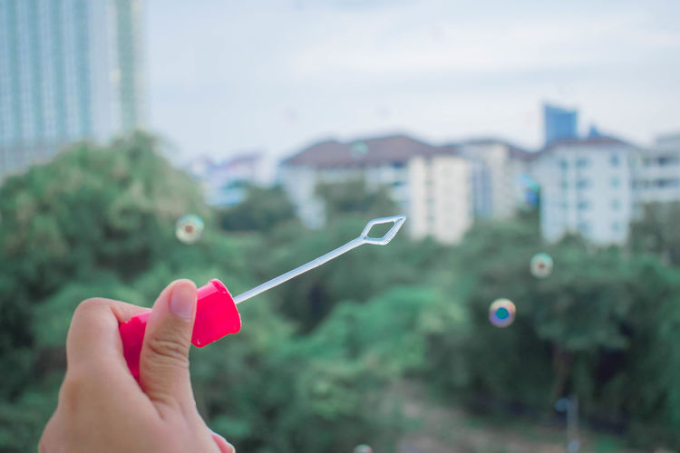 Close-up of hand holding bubble wand against building in city
