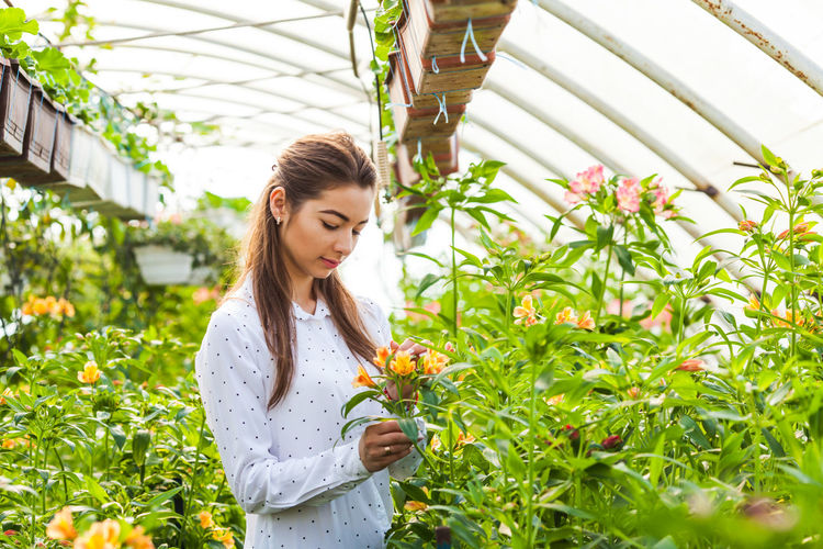 Beautiful woman standing by flowering plants