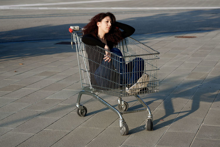 View of woman sitting in shopping cart outdoors