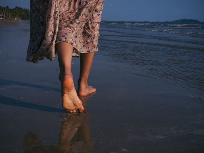 Women who wear vintage dresses are walking on the beach with excitement to relax. This summer, let's go to the sea. Water Beach Low Section Land Real People barefoot One Person Human Body Part Human Leg Lifestyles Sea Body Part Nature Leisure Activity Day Women Standing Sand Outdoors Human Foot