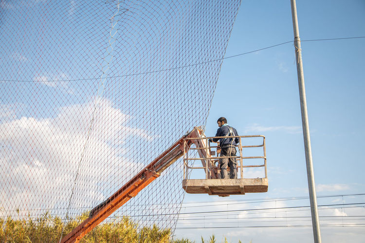 Low angle view of man working on fence