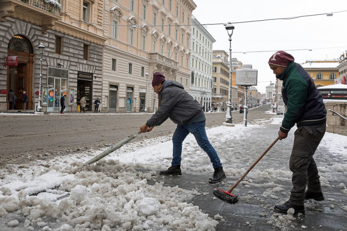 Rome, Italy - February 26, 2018: An exceptional weather event causes a cold and cold air across Europe, including Italy. Snow comes in the capital, covering streets and monuments of a white white coat. In the picture some people sweep the snow from the sidewalk in Via Nazionale. City City Life Cleaning Lifestyle Wintertime Adult Adults Only Architecture Building Exterior Built Structure Cleaning Cold Temperature Day Full Length Manual Worker Men Outdoors People Real People Snow Street Teamwork Warm Clothing Winter Working