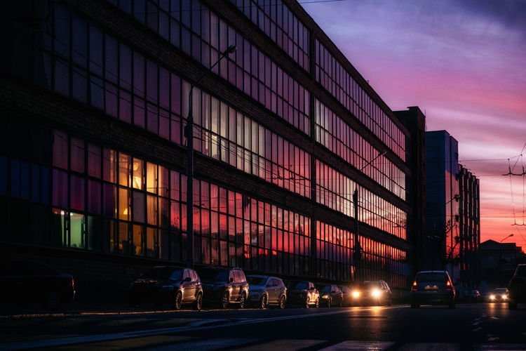 Glass building with reflected evening city and vibrant violet, orange and red sunset sky in it and cars on street, Minsk, Belarus Architecture Building Exterior City Transportation Built Structure Car Sunset Street Sky Cloud - Sky Illuminated City Life Office Building Exterior Dusk Road Colorful Minsk Belarus Glass Reflection Capture Tomorrow 2018 In One Photograph