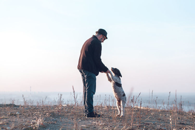 Man with dog standing on land against sky