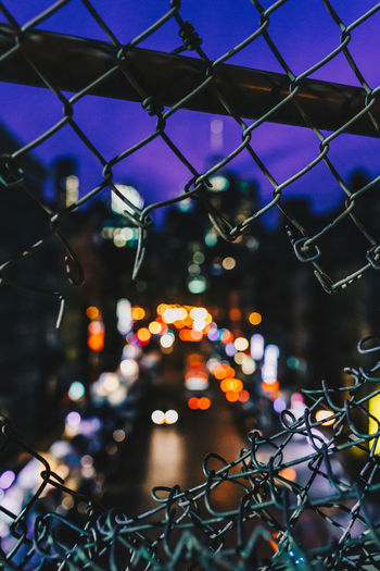 Illuminated lights seen through damaged chainlink fence at night