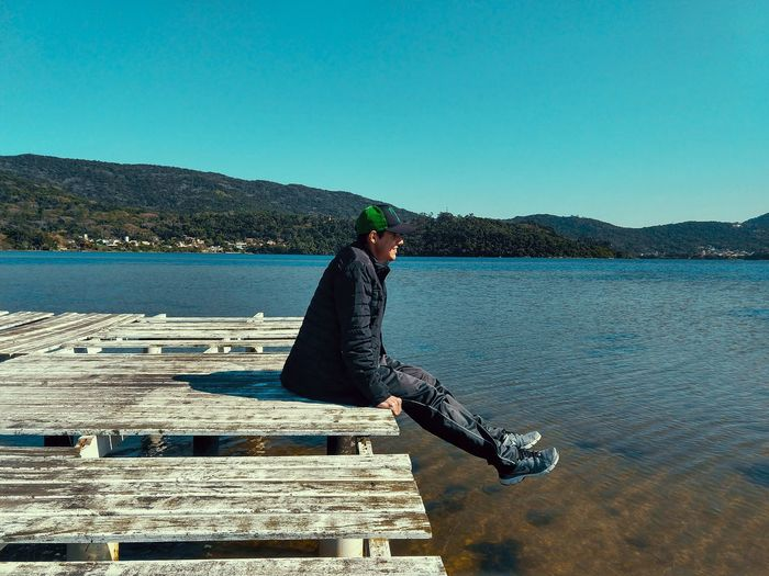 Side View Of Young Man Sitting On Pier Over Lake Against Clear Blue Sky