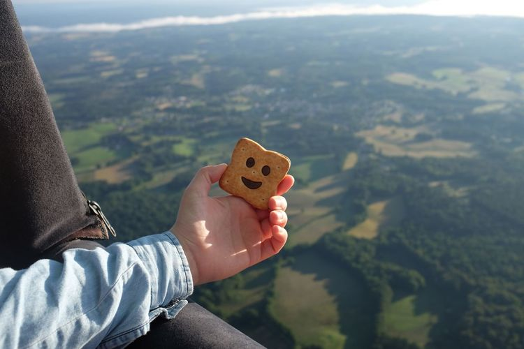Cropped image of person holding biscuit in hot air balloon over landscape