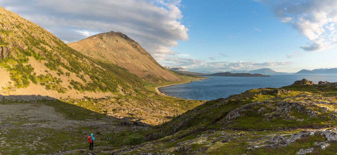 Adventure Beauty In Nature Cloud - Sky Day Dramatic Sky Full Length Hiking Landscape Leisure Activity Lifestyles Mountain Mountain Range Nature Northern Norway Norway One Person Outdoors People Rear View Scenics Sky Taking Photos Tranquil Scene Water Woman Lost In The Landscape