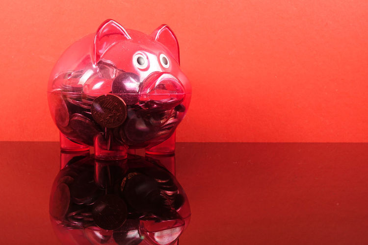 Saving concept with red piggy bank on red background. Piggy Bank Animal Representation Art And Craft Close-up Coin Colored Background Conceptual Photography  Craft Creativity Glass - Material Indoors  Investment Mammal No People Piggy Bank Plastic Red Representation Saving Concept Still Life Studio Shot Table Toy Transparent Wall - Building Feature